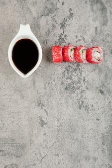 Traditionele sojasaus en sushibroodjes met kaviaar op steenoppervlak.
