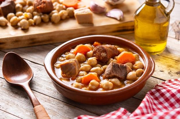 Traditionele spaanse cocido madrileño. kikkererwtenstoofpot op houten tafel