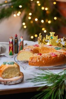 Traditionele spaanse driekoningencake, roscon de reyes met drie koningen, kroon, feestelijke versieringen en kerstverlichting