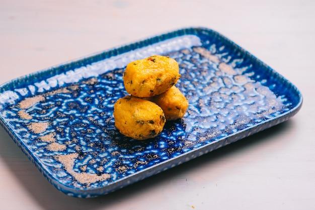 Traditionele spaanse kroketten of croquetas op een blauw bord. tapas eten.