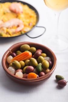 Traditionele spaanse olijven op de plaat. gemengd met wortel en ui