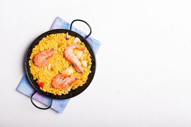 Traditionele spaanse paella met zeevruchten. bereid in traditionele pan