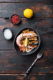 Traditionele spaanse paella met zeevruchten, bereid in wook op oude donkere houten achtergrond