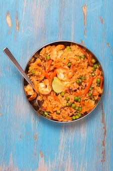 Traditionele spaanse paëllaschotel met zeevruchten, erwten, rijst en kip