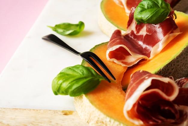 Traditionele spaanse tapas jamon iberico met basilicum en meloen op marmeren serveerplank over roze achtergrond. bovenaanzicht. plat leggen.