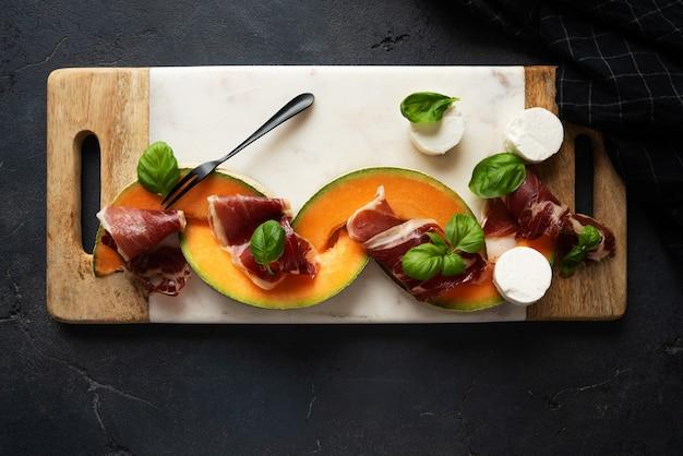 Traditionele spaanse tapas jamon iberico met geitenkaas, basilicum, meloen op marmeren serveerplank over rustieke achtergrond. bovenaanzicht. plat leggen.