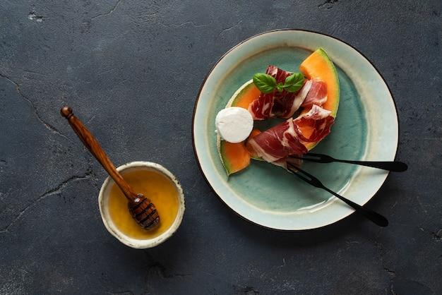 Traditionele spaanse tapas jamon iberico met geitenkaas, meloen en honing over rustieke achtergrond. bovenaanzicht. plat leggen