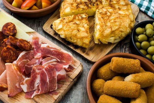 Traditionele spaanse tapas. kroketten, olijven, omelet, ham en patatas bravas op houten tafel