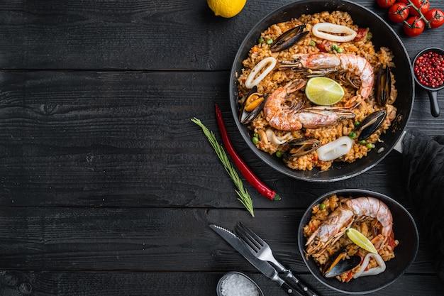 Traditionele spaanse zeevruchtenpaella in pan en kom met rijst, erwten, garnalen, mosselen en inktvis op zwarte houten planken