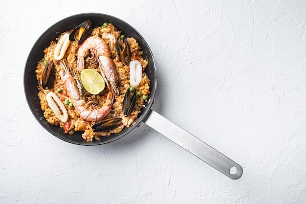 Traditionele spaanse zeevruchtenpaella in pan op witte achtergrond