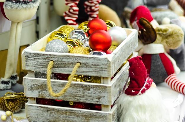 Traditionele speelgoedbeeldjes voor huisdecor. doos met gouden, zilveren, rode glazen bollen op de kerstboom voor het nieuwe jaar.