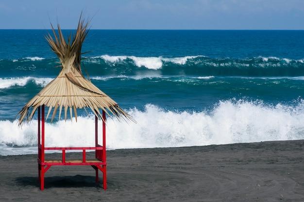 Traditionele strandzonwering, geselecteerde focus in pantai dewa ruci purworejo, indonesië, met wazige blauwe indische oceaan op de achtergrond