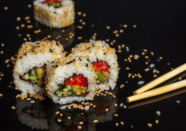 Traditionele sushi en eetstokjes - philadelphia met zalm, avocado en kaas.