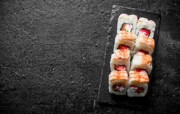 Traditionele sushi rolt met garnalen op een stenen bord. op zwarte rustieke tafel