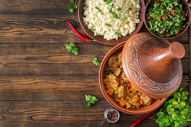 Traditionele tajine gerechten, couscous en verse salade op rustieke houten tafel. tajine lamsvlees en pompoen. bovenaanzicht plat leggen
