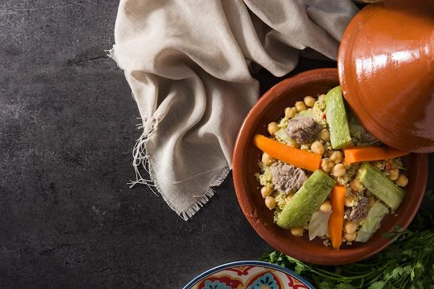 Traditionele tajine met groenten, kikkererwten, vlees en couscous op zwart.