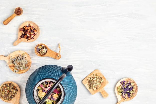 Traditionele theeceremonie-opstelling, theepot en verschillende soorten tisanes met kruiden en gedroogd fruit. tisane detox, ontspanning, genezing, gezonde troost, theetijd concept. bovenaanzicht, plat leggen, kopie ruimte