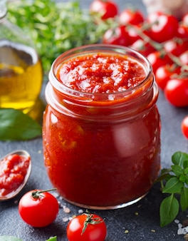 Traditionele tomatensaus in een glazen pot met verse kruiden, tomaten en olijfolie. detailopname.
