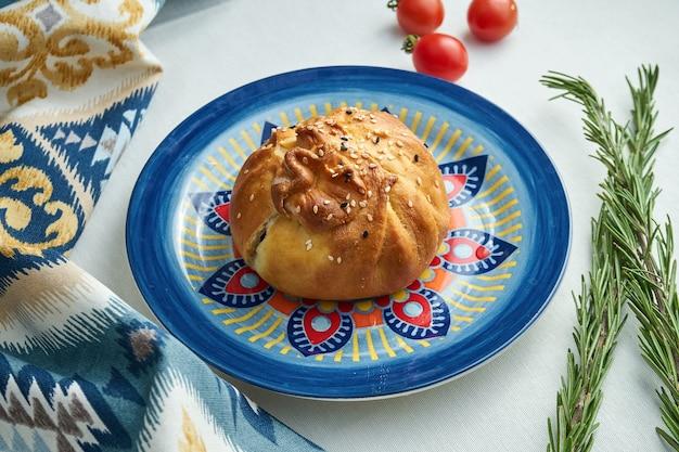Traditionele turkse en krim-tataarse taarten met vlees of samsa in een gevormde plaat op wit