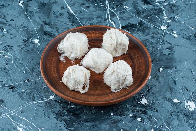 Traditionele turkse katoenen snoepjes op een houten plaat, op de blauwe achtergrond. Gratis Foto