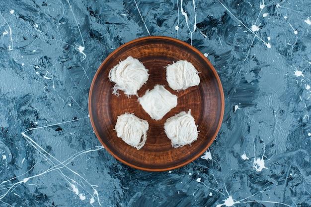 Traditionele turkse katoenen snoepjes op een houten plaat, op de blauwe achtergrond.
