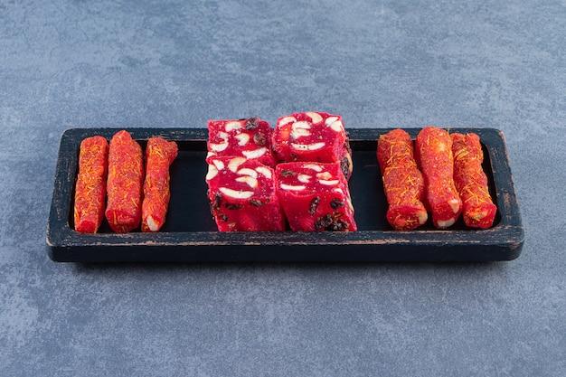 Traditionele turkse lekkernijen op een houten bord op het marmeren oppervlak