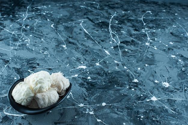 Traditionele turkse suikerspin in een kom, op de blauwe achtergrond.