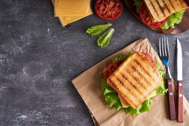Traditionele vegetarische sandwich met tomaten en kaas op een grijze stenen tafel copyspace