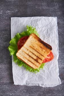 Traditionele vegetarische sandwich met tomaten en kaas op een grijze stenen tafel verticale close-up