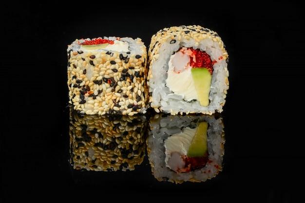 Traditionele verse japanse sushibroodjes op een zwarte achtergrond