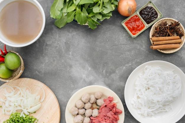 Traditionele vietnamese noedelsoepen pho in kommen, betonnen achtergrond. vietnamese rundvleessoep pho bo, close-up. aziatisch/vietnamees eten. vietnamees diner. pho bo-maaltijd. bovenaanzicht. gezond