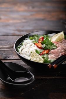 Traditionele vietnamese soep pho bo met rundvlees en noedels op een houten oppervlak, selectieve aandacht