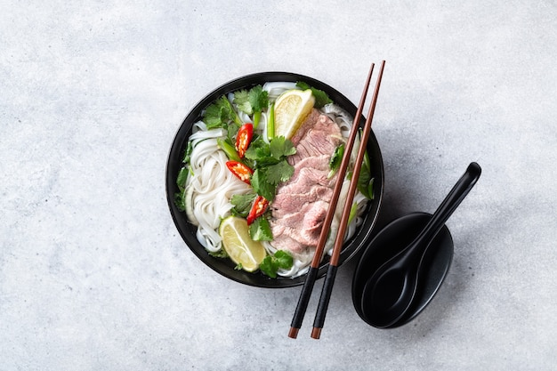 Traditionele vietnamese soep pho bo met rundvlees en rijstnoedels op een concrete achtergrond, van bovenaf bekijken