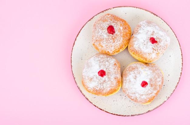 Traditionele voedseldonuts met suikerglazuursuiker en jam. concept en achtergrond joodse feestdag chanoeka.
