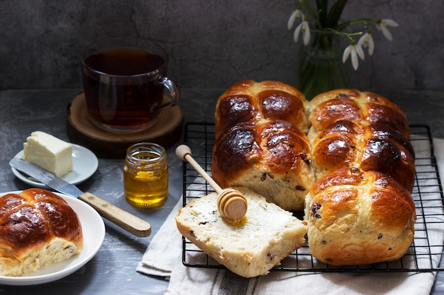 Traditionele warme kruisbroodjes met honing en boter op een betonnen ondergrond