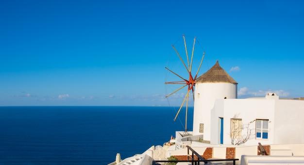 Traditionele windmolen en appartementen in oia dorp, santorini, griekenland