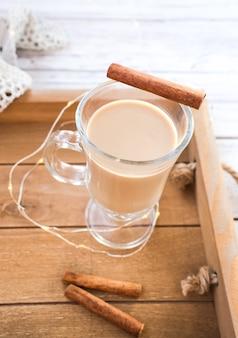 Traditionele winter advocaat in glazen mok met melk, rum en kaneel, kerstversiering.
