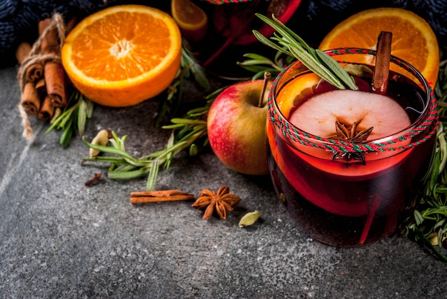 Traditionele winter- en herfstdranken kerst- en thanksgiving-cocktails glühwein met sinaasappelappelrozemarijn, kaneel en kruiden op een donkere stenen achtergrond