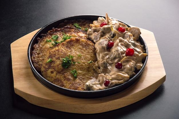 Traditionele wit-russische draniki met een garnituur van kipstukjes met zure roomsaus en gebakken groenten