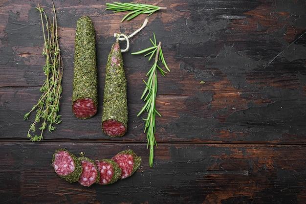 Traditionele worst salami fuet, in plakjes gesneden op een donkere houten ondergrond, bovenaanzicht met ruimte voor tekst.