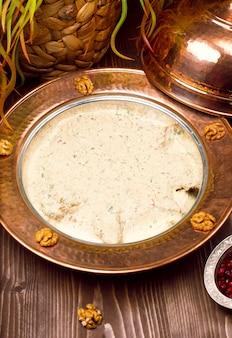 Traditionele yayla-soep (yoghurtsoep) in koperen plaat met walnoten