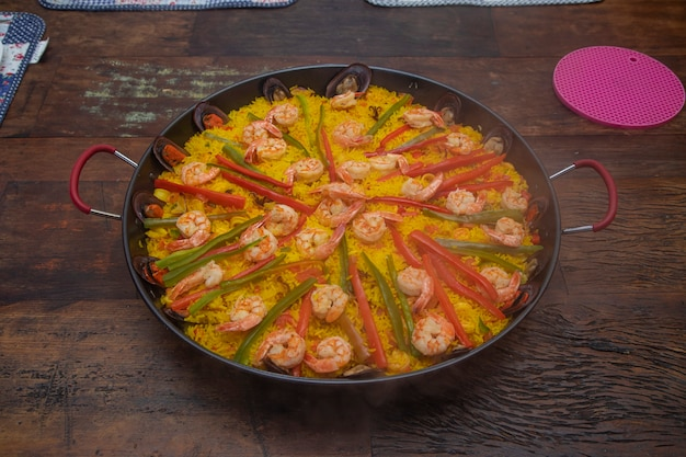 Traditionele zeevruchten paella in de koekenpan op een houten oude tafel.