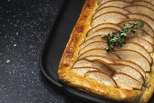 Traditionele zelfgemaakte biologische appeltaart op donkere tafel. gezond foood-concept
