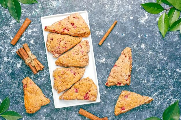 Traditionele zelfgemaakte engelse scones met bevroren frambozen en kaneel, bovenaanzicht