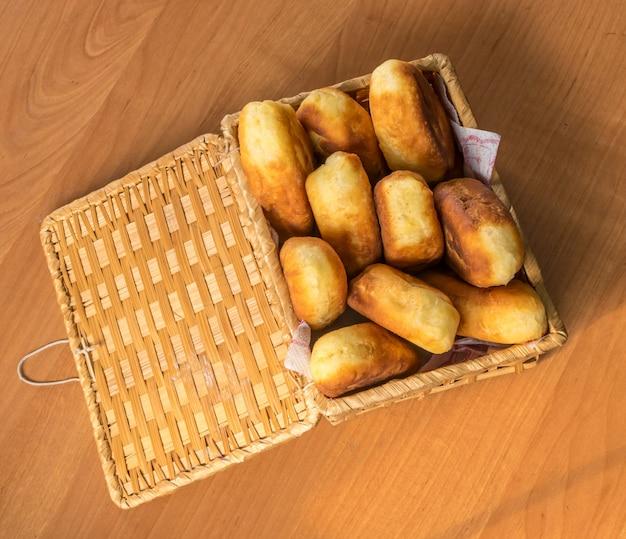 Traditionele zelfgemaakte gebakken pasteitjes of taarten met jam in een rieten mand. gebakken russische pirozhki gemaakt van gistdeeg in rustieke stijl