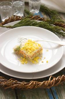 Traditionele zelfgemaakte salade mimosa met vis, groenten en eieren. een portie. sovjet-leven. rustieke stijl, selectieve aandacht.