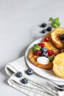 Traditionele zoete wentelteefjes met bosbessen, gedroogde kersen en munt zoet ontbijt.