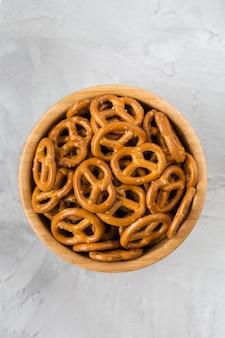Traditionele zoute mini-krakelingen in houten kom op een grijze achtergrond