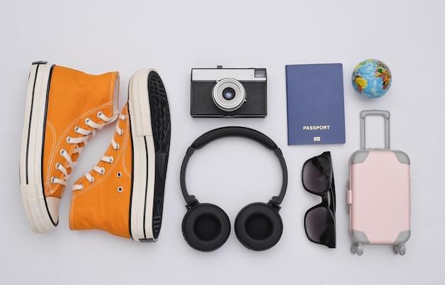 Trafel plat gelegd. stereo koptelefoon, sneakers en reisaccessoires op witte achtergrond. bovenaanzicht