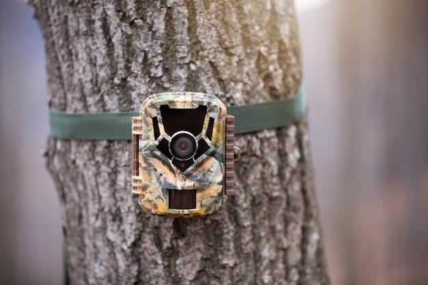 Trail camera voor wildlife monitoring bevestigd aan een boom met groene riem